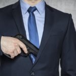 businessman with a gun, grey background with copy space